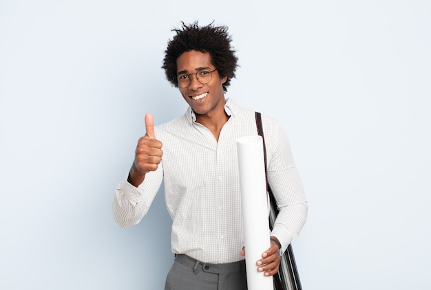 Jonge zwarte afro man die zich trots, zorgeloos, zelfverzekerd en gelukkig voelt, positief glimlacht met duimen omhoog