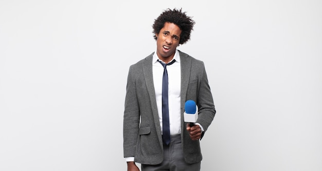 Jonge zwarte afro man die zich verbaasd en verward voelt, met een domme, verbijsterde uitdrukking op zoek naar iets onverwachts