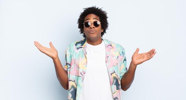 Jonge zwarte afro man die zich verbaasd en verward voelt, twijfelt, weegt of verschillende opties kiest met een grappige uitdrukking