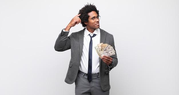 Jonge zwarte afro man die zich verbaasd en verward voelt, zijn hoofd krabt en naar de zijkant kijkt