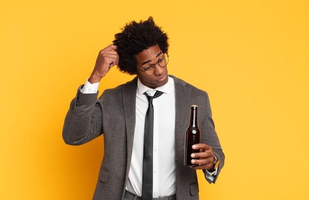 Jonge zwarte afro-man die zich verbaasd en verward voelt, zijn hoofd krabt en opzij kijkt