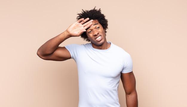Jonge zwarte afro man die zich verdrietig, gefrustreerd, nerveus en depressief voelt, gezicht bedekt met beide handen