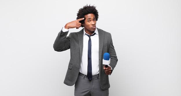 Jonge zwarte afro-man die zich verward en verbaasd voelt en laat zien dat je gek, gek of gek bent