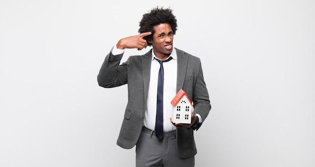 Jonge zwarte afro man die zich verward en verbaasd voelt, laat zien dat je gek, gek of gek bent