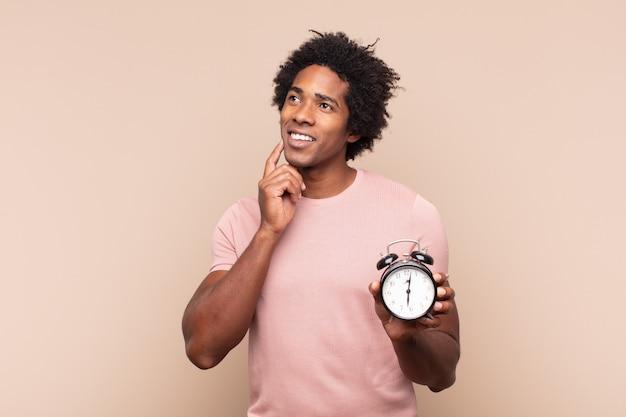 Jonge zwarte afro man gelukkig lachend en dagdromen of twijfelen, op zoek naar de kant