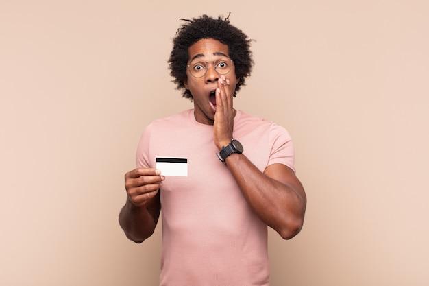 Jonge zwarte afro man geschokt en bang, doodsbang kijkend met open mond en handen op de wangen