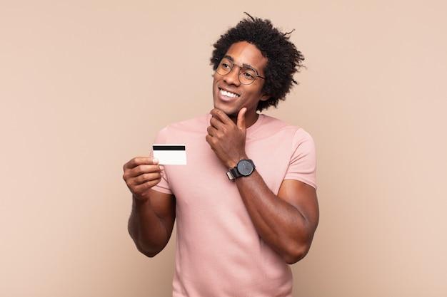 Jonge zwarte afro-man glimlachend met een gelukkige, zelfverzekerde uitdrukking met de hand op de kin, zich afvragend en opzij kijkend