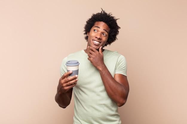 Jonge zwarte afro man glimlachend met een gelukkige, zelfverzekerde uitdrukking met hand op de kin, zich afvragend en naar de zijkant kijkend