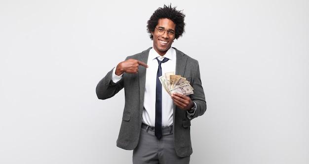 Jonge zwarte afro man glimlachend vol vertrouwen wijzend naar eigen brede glimlach, positieve, ontspannen, tevreden houding