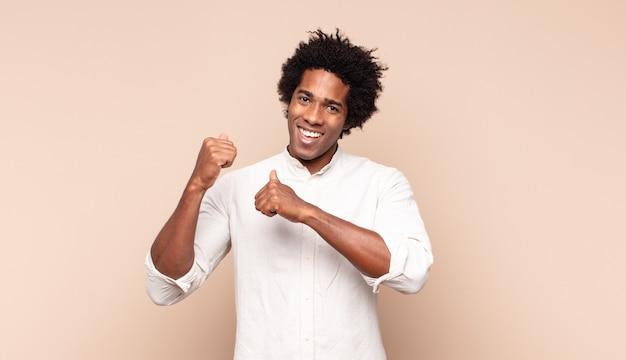 Jonge zwarte afro man glimlachend vrolijk en terloops wijzend naar kopie ruimte aan de zijkant, gelukkig en tevreden gevoel