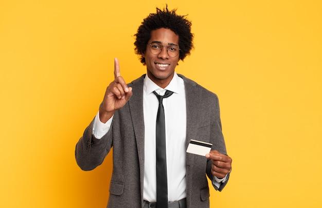 Jonge zwarte afro-man glimlacht en ziet er vriendelijk uit, toont nummer één of eerste met hand naar voren, aftellend