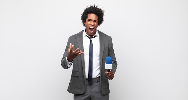 Jonge zwarte afro man kijkt boos, geïrriteerd en gefrustreerd schreeuwend wtf of wat is er mis met je
