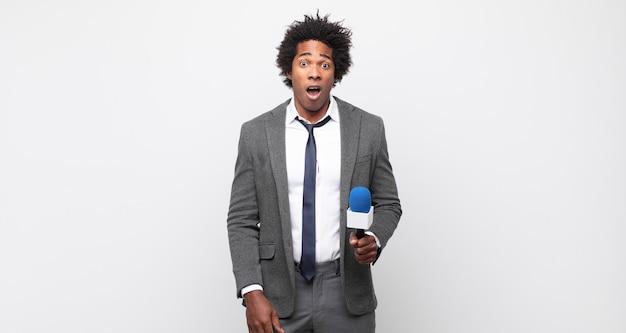 Jonge zwarte afro man kijkt erg geschokt of verrast, starend met open mond en zegt wow