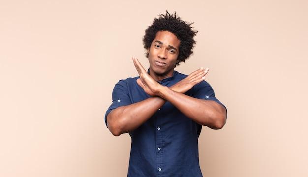 Jonge zwarte afro man kijkt ongeduldig en boos, wijzend op horloge, vraagt om stiptheid, wil op tijd zijn