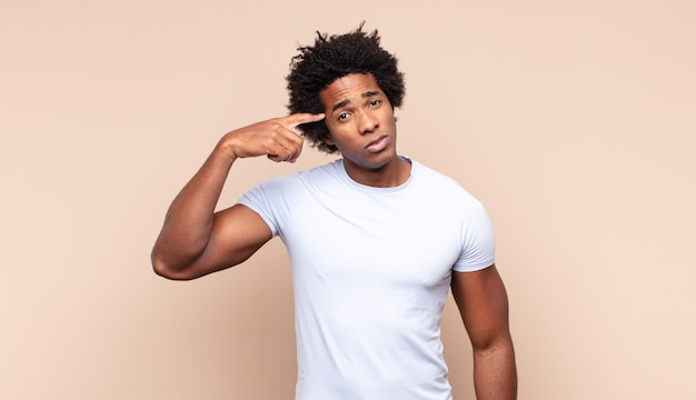 Jonge zwarte afro man lacht vrolijk en opgewekt, zwaait met de hand, verwelkomt en begroet je, of neemt afscheid