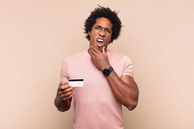 Jonge zwarte afro-man met mond en ogen wijd open en hand op kin, onaangenaam geschokt, wat zeggend of wauw