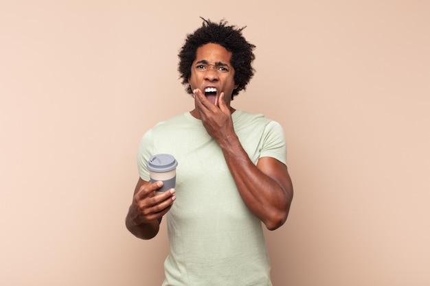 Jonge zwarte afro man met mond en ogen wijd open en hand op kin, onaangenaam geschokt, zeggend wat of wauw