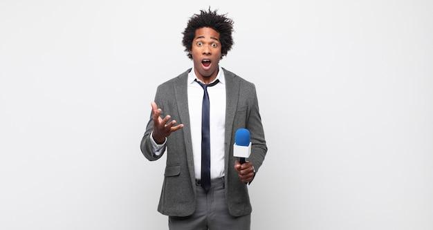 Jonge zwarte afro man met open mond en verbaasd, geschokt en verbaasd met een ongelooflijke verrassing