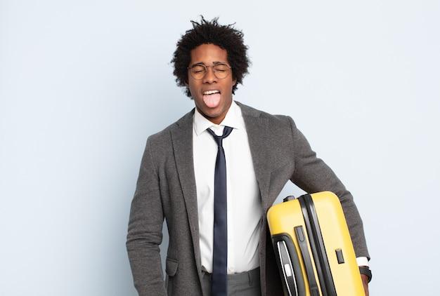 Jonge zwarte afro man met vrolijke, zorgeloze, rebelse houding, grappen maken en tong uitsteken, plezier maken