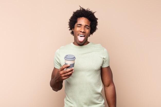 Jonge zwarte afro man met vrolijke, zorgeloze, rebelse houding, grappen maken en tong uitsteken