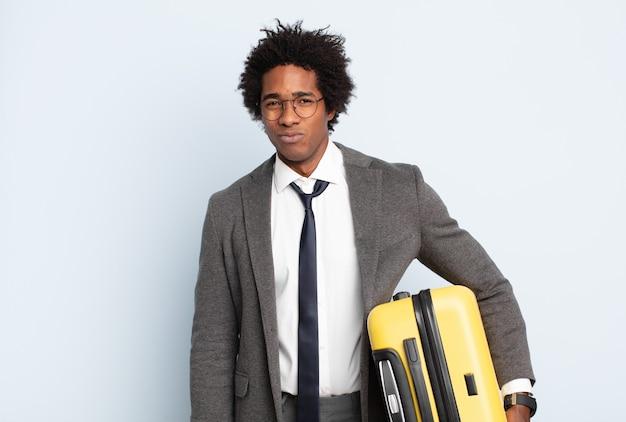 Jonge zwarte afro man verdrietig en zeurderig met een ongelukkige blik, huilend met een negatieve en gefrustreerde houding