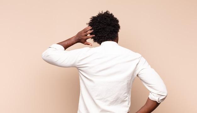 Jonge zwarte afro-man voelt zich geen idee en verward, denkt een oplossing, met de hand op de heup en de andere op het hoofd, achteraanzicht