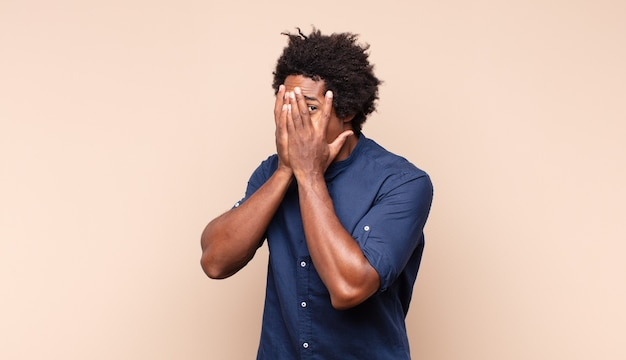 Jonge zwarte afro man vraagt om stilte en stilte, gebaart met de vinger voor de mond, zegt shh of houdt een geheim