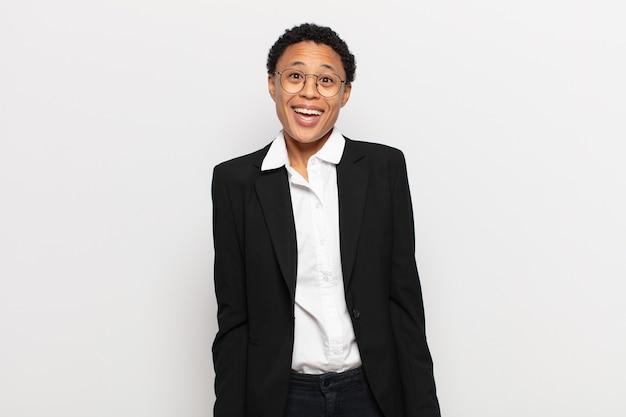 Jonge zwarte afro-vrouw die blij en aangenaam verrast kijkt, opgewonden met een gefascineerde en geschokte uitdrukking