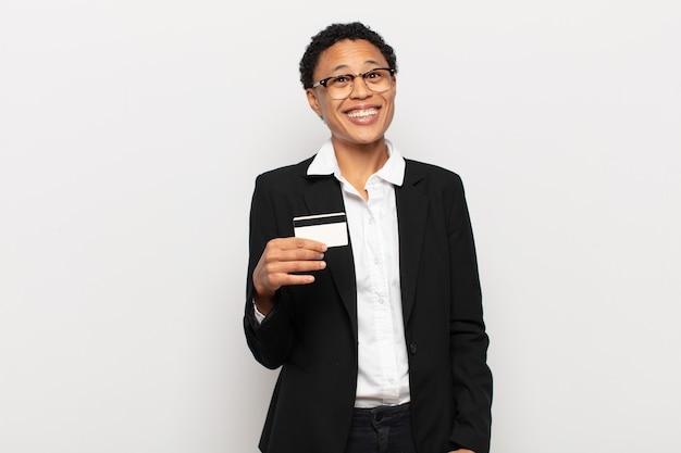 Jonge zwarte afro-vrouw die er blij en aangenaam verrast uitziet, opgewonden met een gefascineerde en geschokte uitdrukking