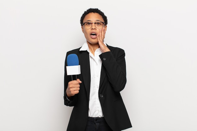 Jonge zwarte afro vrouw die geschokt en bang is, doodsbang kijkt met open mond en handen op de wangen