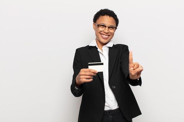 Jonge zwarte afro vrouw die trots en zelfverzekerd glimlacht en nummer één triomfantelijk laat poseren, zich een leider voelt