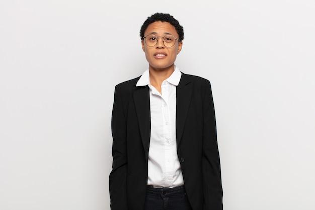 Jonge zwarte afro-vrouw die verbaasd en verward kijkt, lip bijtend met een nerveus gebaar, het antwoord op het probleem niet weet