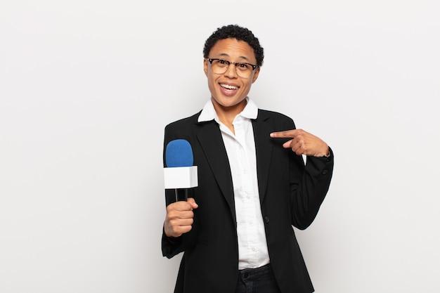 Jonge zwarte afro-vrouw die zich blij, verrast en trots voelt en naar zichzelf wijst met een opgewonden, verbaasde blik