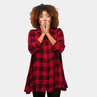 Jonge zwarte afro vrouw erg bang en bang verborgen