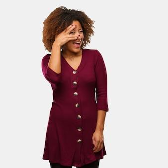 Jonge zwarte afro-vrouw in verlegenheid gebracht en tegelijkertijd lachen
