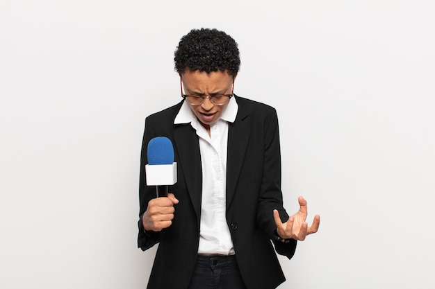 Jonge zwarte afro vrouw kijkt boos, geïrriteerd en gefrustreerd schreeuwend wtf of wat is er mis met jou