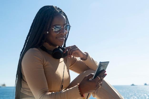 Jonge zwarte afro vrouw lachend kijken naar haar mobiel, buitenshuis met blauwe lucht en zee