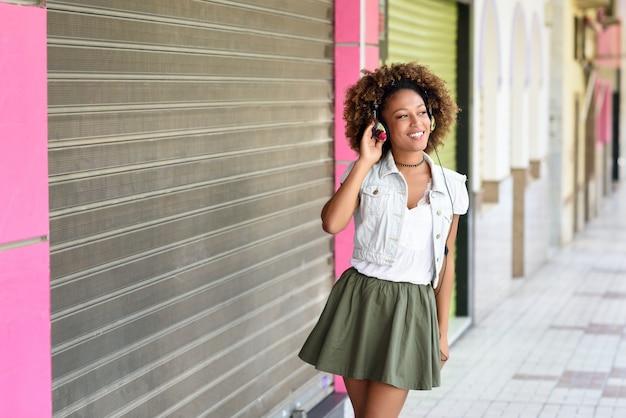 Jonge zwarte, afrokapsel, in stedelijke straat met hoofdtelefoons