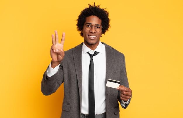 Jonge zwarte afromens die vriendelijk glimlacht kijkt, nummer drie of derde met vooruit hand toont, aftellend