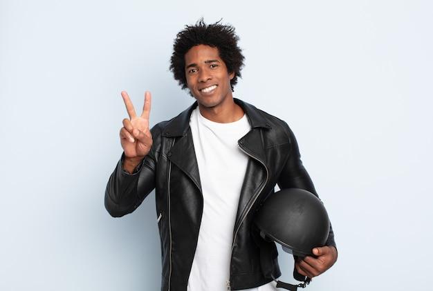 Jonge zwarte afromens die vriendelijk glimlacht kijkt, nummer twee of seconde met vooruit hand toont, aftellend