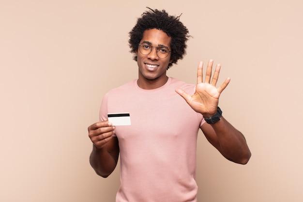 Jonge zwarte afromens die vriendelijk glimlacht kijkt, nummer vijf of vijfde met vooruit hand toont, aftellend