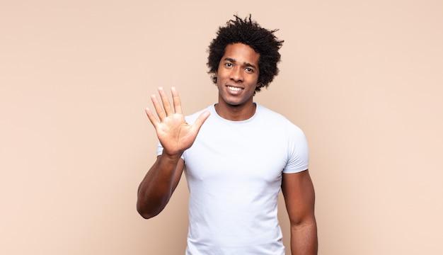 Jonge zwarte afromens die vriendelijk glimlacht kijkt, nummer zes of zesde met vooruit hand toont, aftellend
