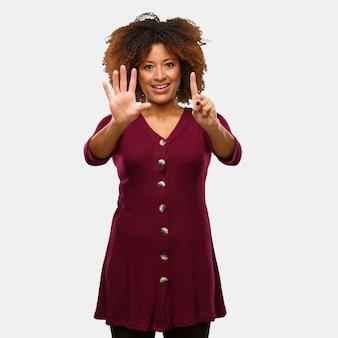 Jonge zwarte afrovrouw die nummer zes toont