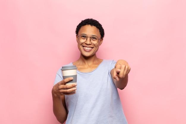 Jonge zwarte afrovrouw die op camera richt met een tevreden, zelfverzekerde, vriendelijke glimlach, die jou kiest