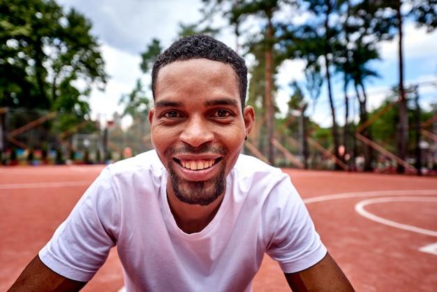 Jonge zwarte basketbalspeler die bij de camera glimlacht