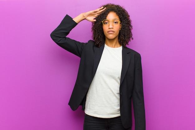 Jonge zwarte bedrijfsvrouw die de camera begroet
