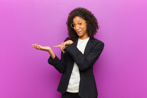 Jonge zwarte bedrijfsvrouw die vrolijk glimlacht en aan exemplaarruimte op palm aan de kant richt, een voorwerp toont of adverteert