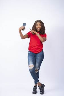 Jonge zwarte dame die haar telefoon vasthoudt en ernaar wijst met opwinding op haar gezicht