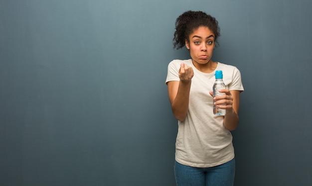 Jonge zwarte die een gebaar van behoefte doet. ze houdt een fles water vast.