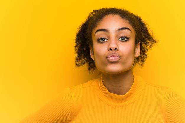 Jonge zwarte die een kus, oranje muur verzendt.